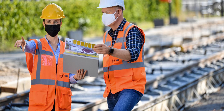 Im Vordergrund stehen eine Bauleiterind und ein Arbeiter und schauen sich Baupläne an. Im Hintergrund sieht man eine Straßenbahn-Baustelle. Beide tragen Helme.