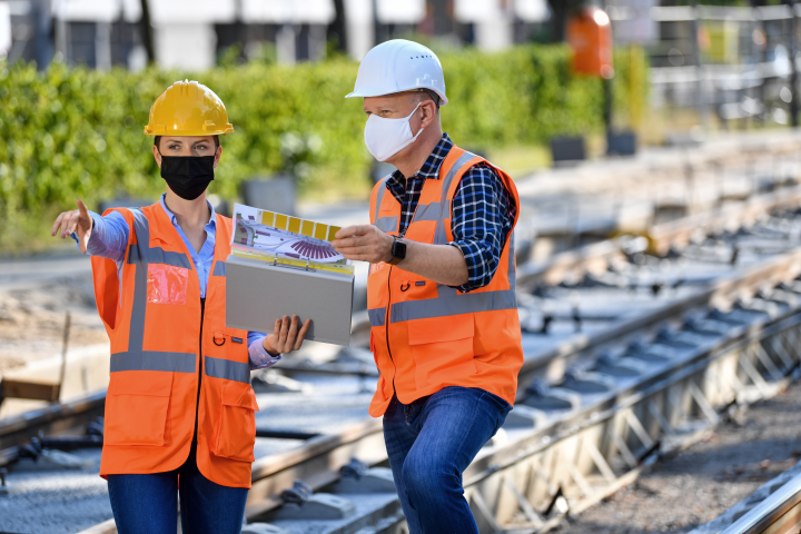 A site manager and a worker are looking at construction plans in the foreground. A tram stop can be seen in the background. Both are wearing helmets.