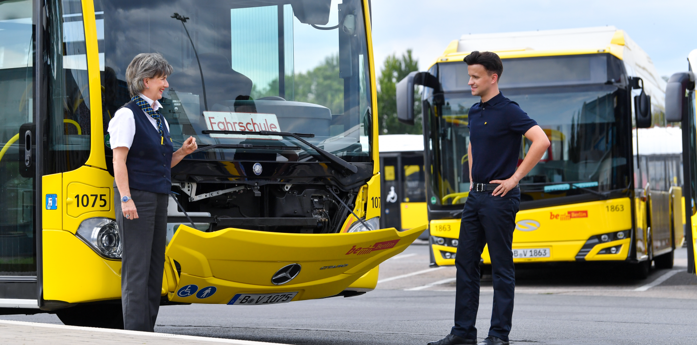 Eine Fahrschullehrerin steht vor einem Bus, an dem die Motorhaube geöffnet ist. Sie zeigt einem jungen Mann einige Teile des Motors und erklärt sie ihm.