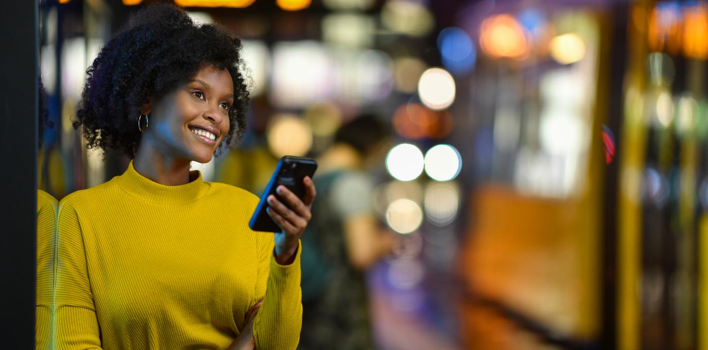 Eine junge Frau lehnt an einer Straßenbahnhaltestelle. Sie schaut dabei auf ihr Handy. Im Hintergrund ist eine Straßennbahn.