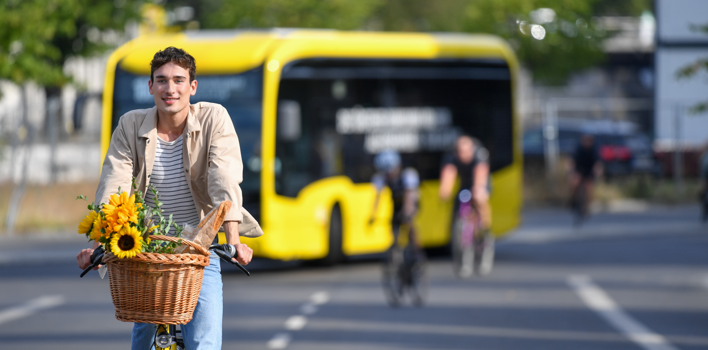 Im Vordergrund sieht man einen Jungen Mann auf einem Fahrrad. Vorne am Fahrrad ist ein Korb mit Sonnenblumen und einen Baguette. Hinten in der Unschärfe steht ein E-Bus