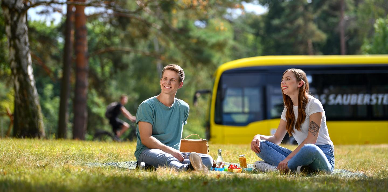 Ein junges Pärchen sitzt auf einer Picknickdecke im Wald auf einer Wiese. Im Hintergrund steht ein E-Bus.