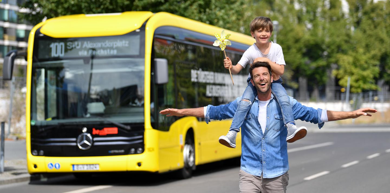 Ein Vater hat seinen sehr jungen Sohn auf den Schultern. Der Junge hat ein kleines gelbes Windrad in der Hand. Beide lachen. Im Hintergrund steht ein E-Bus.