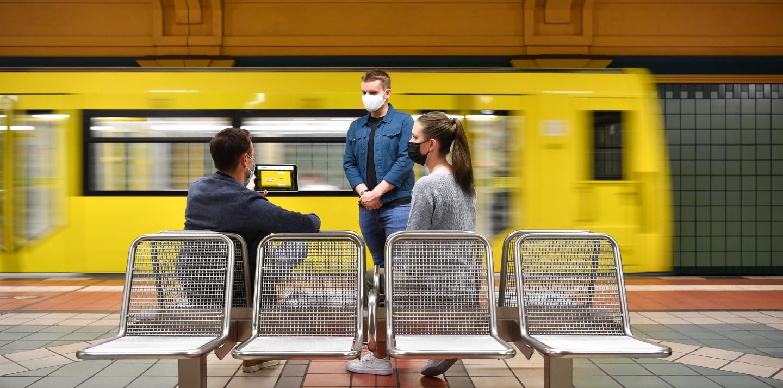Drei Personen befinden sich in einem U-Bahnhof und schauen gemeinsam auf ein iPad. Im Hintergrund fährt eine U-Bahn aus dem Bild.