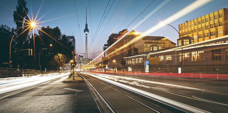 Man sieht Lichtstreifen einer Langzeitbelichtung von einer Straßenbahn und Autos. Im Hintergrund der Fernsehturm.